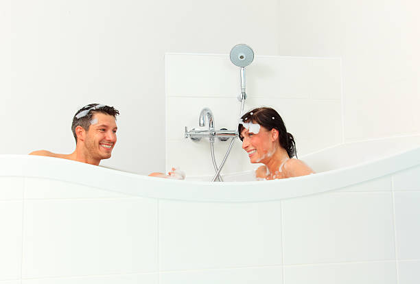 couple bathing together in a foamy shower tub stock photo