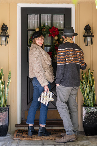 Young millennial boyfriend and girlfriend dressed to impress arrive at the front door with their Christmas gifts.