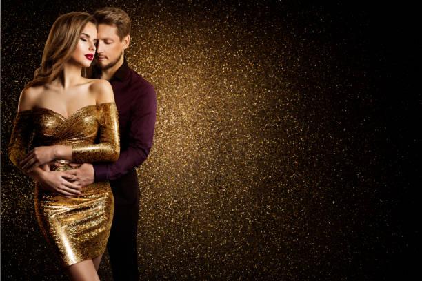 Couple Beauty Portrait, Dreaming Beautiful Woman in Gold dress embracing Elegant Man stock photo