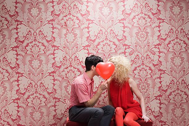 coppia dietro il palloncino a forma di cuore - romanticismo concetto foto e immagini stock