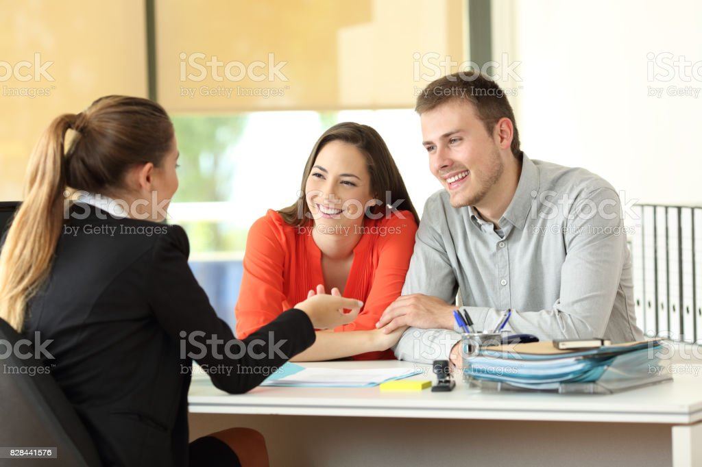 Couple being attended by office worker stock photo