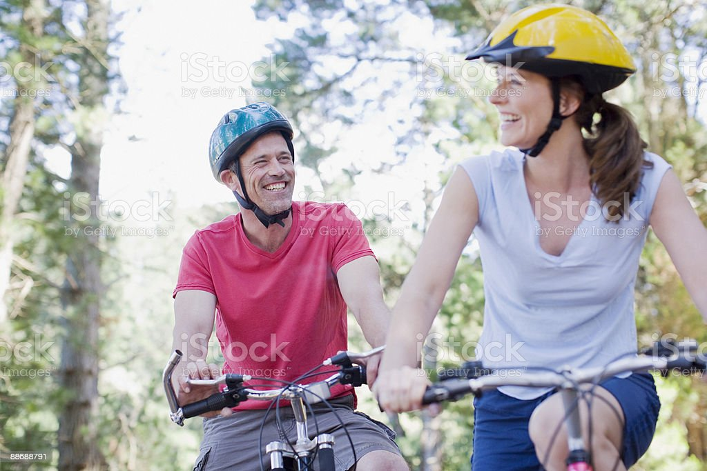 Couple bike riding in forest stock photo
