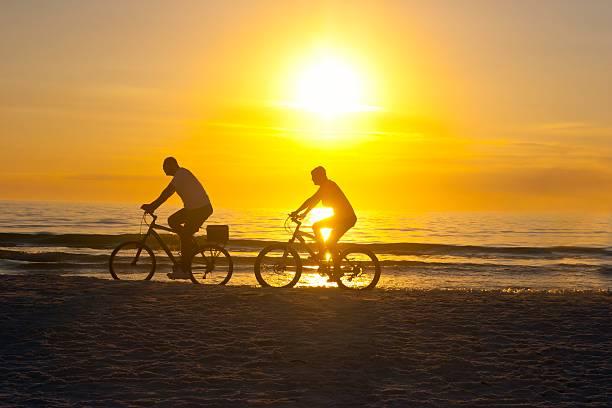 Couple Biking at Sunset on the Beach stock photo