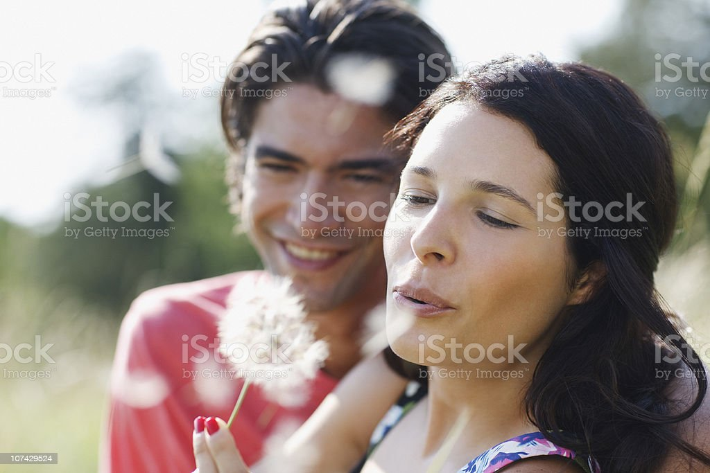 Couple blowing dandelion seeds together royalty-free stock photo