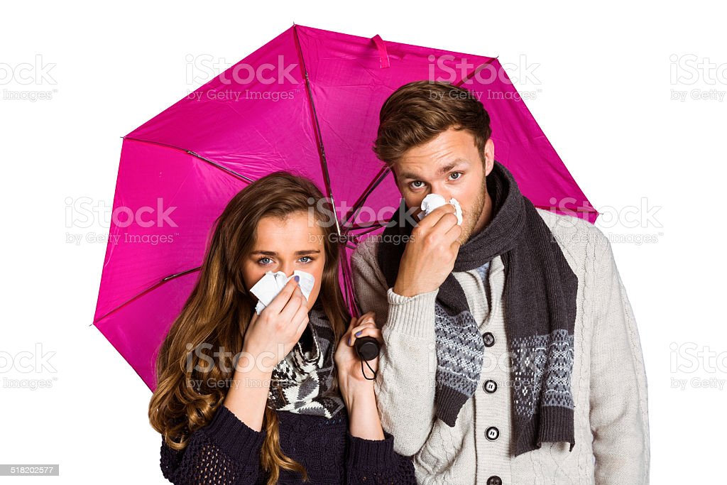 Couple blowing nose while holding umbrella stock photo