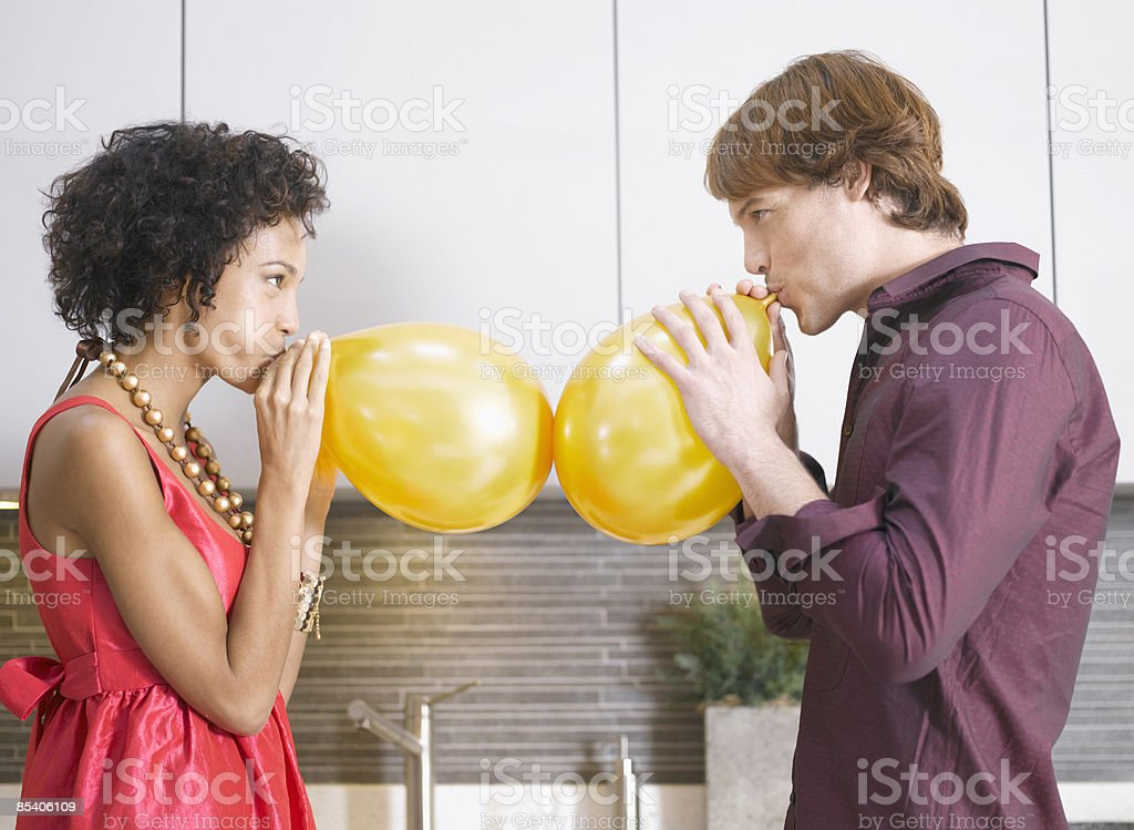 Couple blowing up balloons stock photo