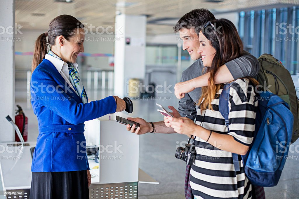 Couple boarding to plane showing smart phone ticket at gate stock photo