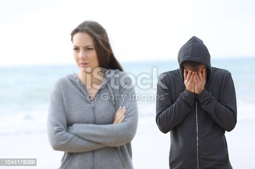 istock Couple break up on the beach with a girl leaving man 1044178066