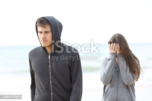 istock Couple break up on the beach with a man leaving girl 1044177974