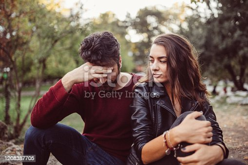 Young couple in the park feeling disappointed