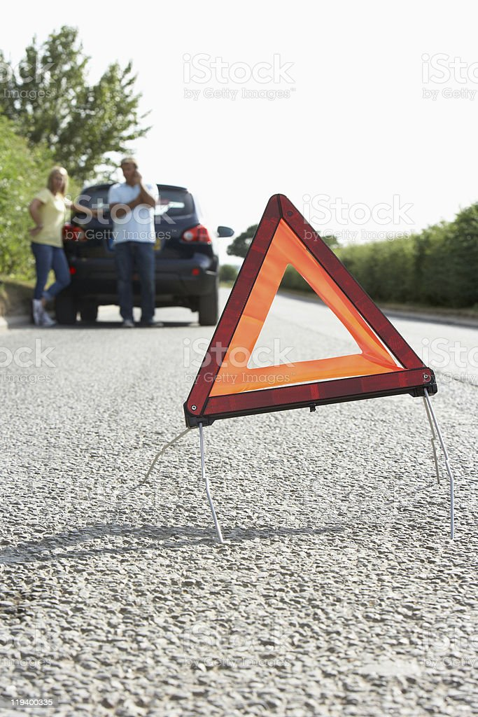 Couple Broken Down On Country Road With Hazard Warning Sign royalty-free stock photo