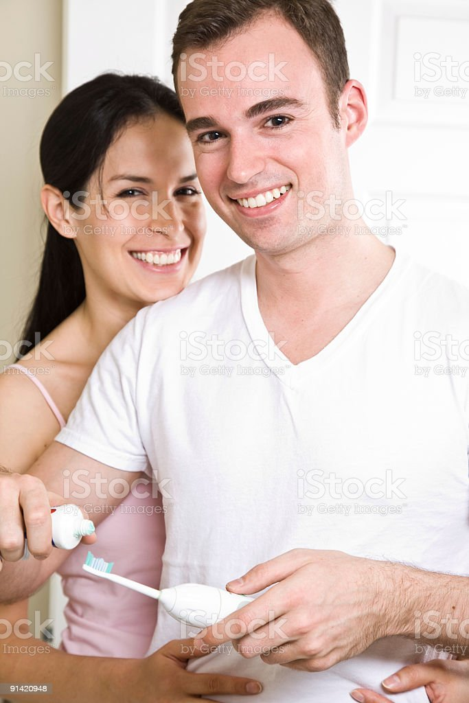 Couple brushing teeth in the bathroom royalty-free stock photo