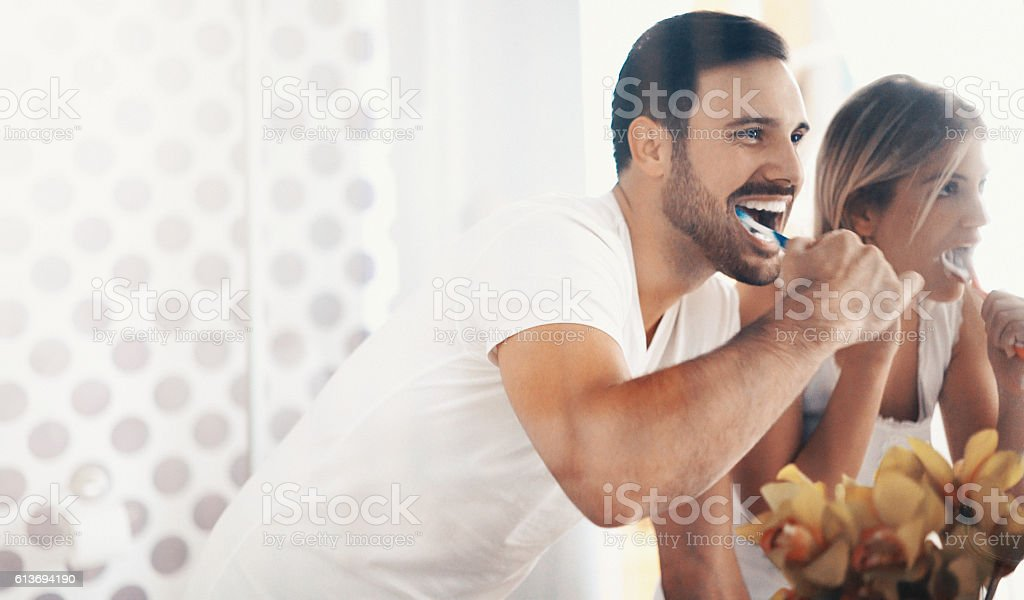 Couple brushing teeth in the morning. stock photo