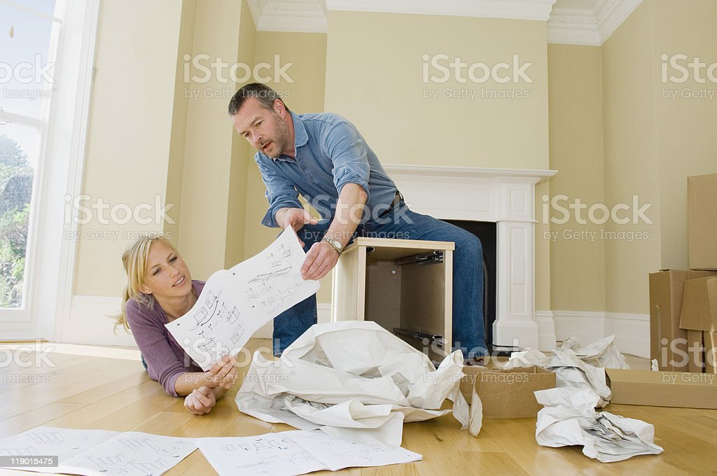 Couple building cabinet in new home stock photo