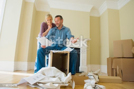 istock Couple building cabinet in new home 119015476
