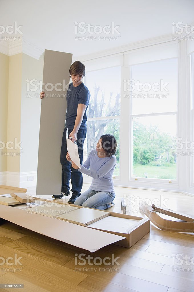 Couple building furniture in new home stock photo