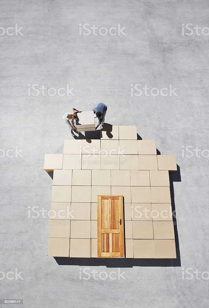 Couple building house outline on sidewalk royalty-free stock photo