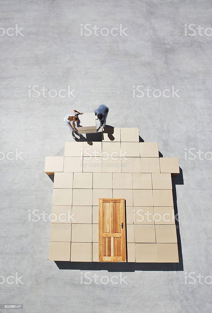 Couple building house outline on sidewalk stock photo