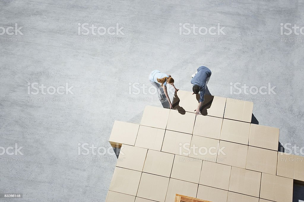 Couple building house outline on sidewalk stock photo