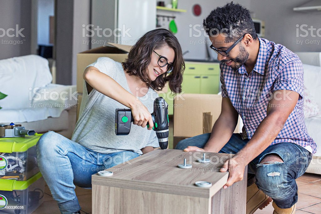 Couple building some furniture units for the new home stock photo