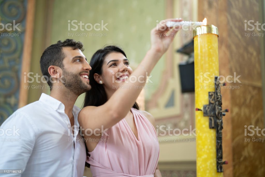 Couple burning candle in a religious celebration stock photo