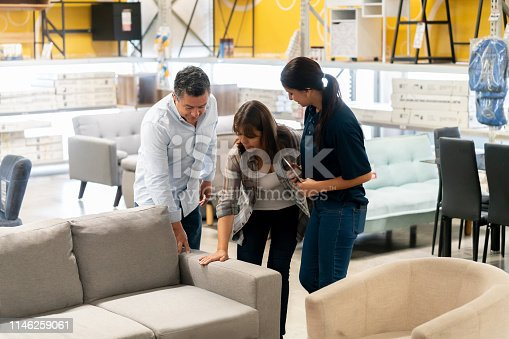 Happy couple buying a couch at a home improvement store and talking to a saleswoman - business concepts
