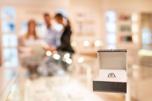 Couple buying an engagement ring at a jewelry store Couple buying an engagement ring at a jewelry store – focus on foreground jeweller stock pictures, royalty-free photos & images