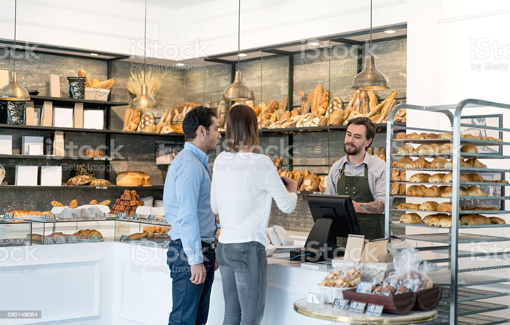 Couple buying bread at the bakery stock photo