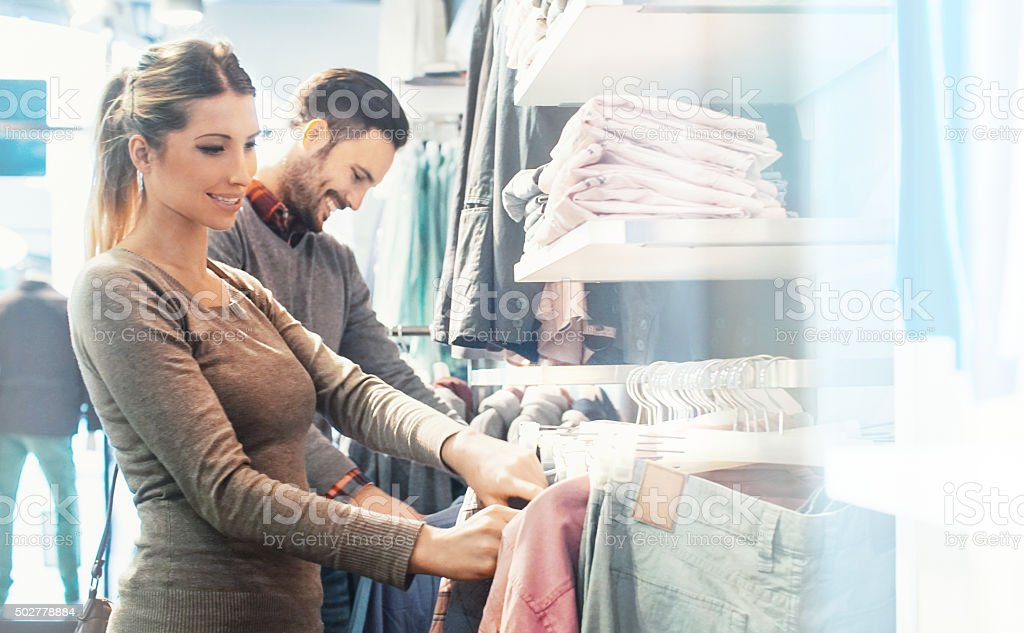 Couple buying clothes at department store. stock photo