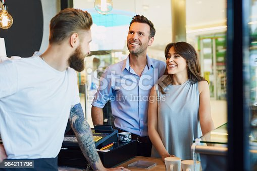 597640822 istock photo Couple buying coffee at cafeteria, talking with barista 964211796