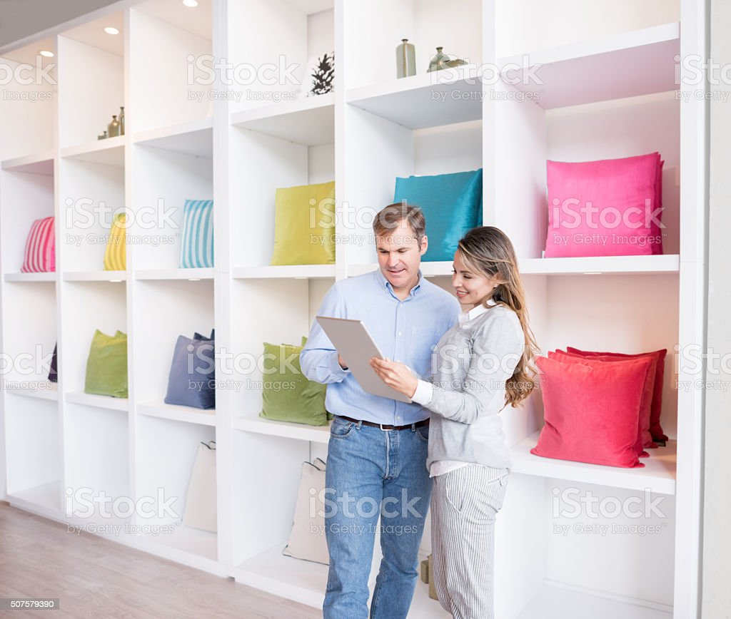 Couple buying cushions at a furniture store and looking at the...