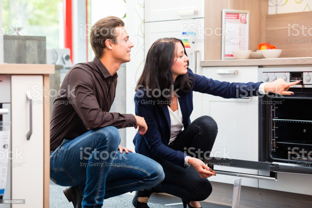 Couple buying domestic kitchen in showroom royalty-free stock photo