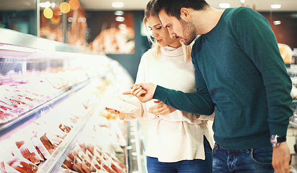 couple buying fresh meat in supermarket. - meat stock photos and pictures