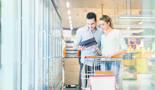 커플입니다 구매 냉동 슈퍼마켓. - 냉동식품 뉴스 사진 이미지