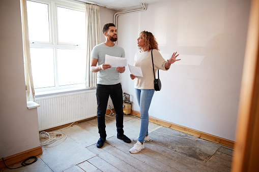 istock Couple Buying House For First Time Looking At House Survey In Room To Be Renovated 1083736208