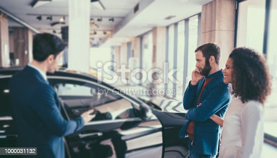 Young woman and her husband in the showroom purchasing new car