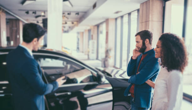 Couple buying new car Young woman and her husband in the showroom purchasing new car car salesperson stock pictures, royalty-free photos & images