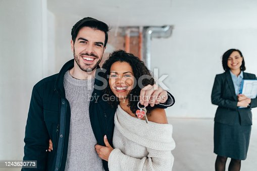 Young couple viewing new property with real estate agent