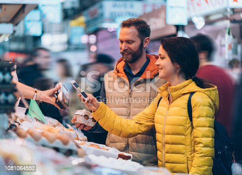 Smiling couple buying fresh eggs and paying contactless with smartphone