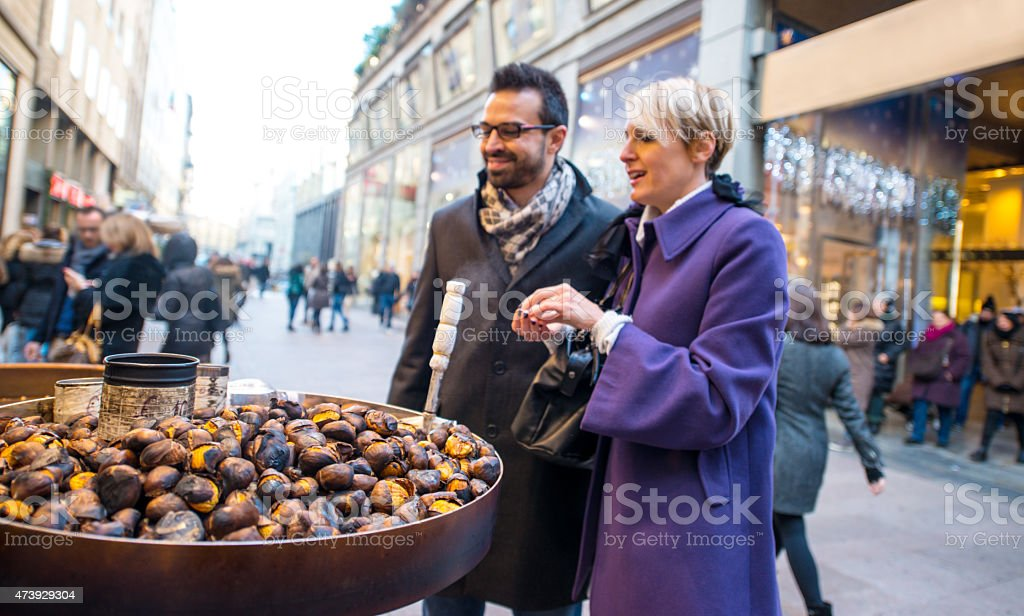 Couple buying roasted chestnuts on Milan street stock photo