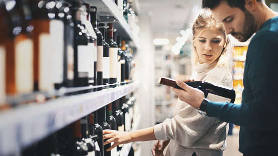 Closeup side view of late 20's couple choosing some red wine at local supermarket. The guy is holding on of the bottles and they're both reading the label on the back. Big selection of unrecognizable red wines in front of them.
