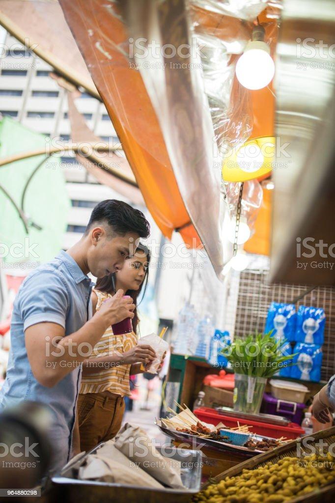 Couple buying street food at the Jalan Petaling market royalty-free stock photo