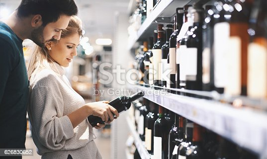 Closeup of early 30's couple doing some home shopping in local supermarket. They are walking down wine aisle and choosing a bottle of red wine. Side view.