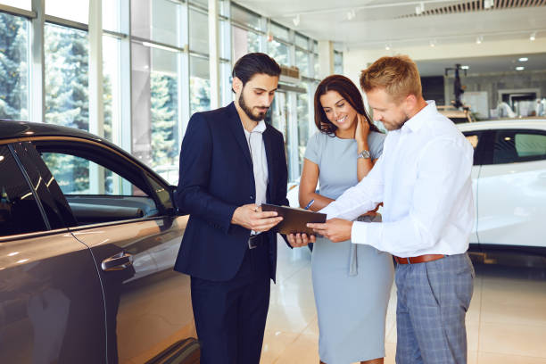 A couple buys a car in a car showroom. stock photo