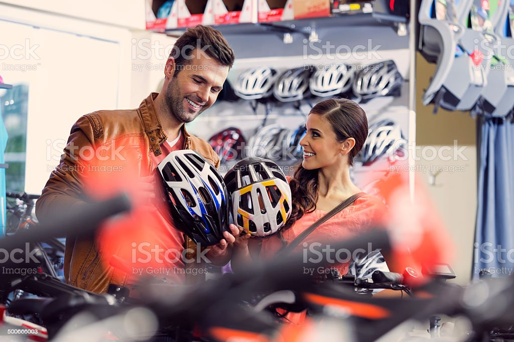 Couple bying bike helmets Cheerful couple watching a helmets in a bike store. Adult Stock Photo