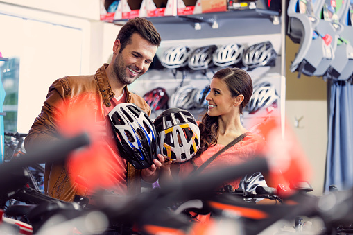 Couple Bying Bike Helmets Stock Photo - Download Image Now