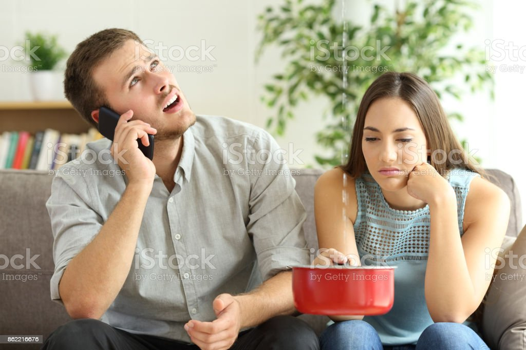 Couple calling insurance for home leaks stock photo
