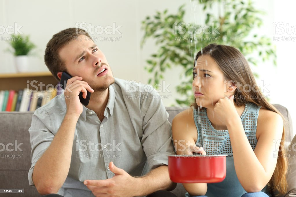 Couple callling to insurance for home leaks royalty-free stock photo