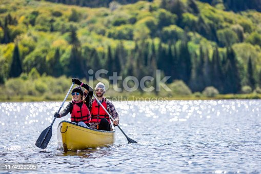 A man and a woman are canoeing on a calm lake on a beautiful sunny day at Parc national du Mont-Tremblant, Quebec, Canada.