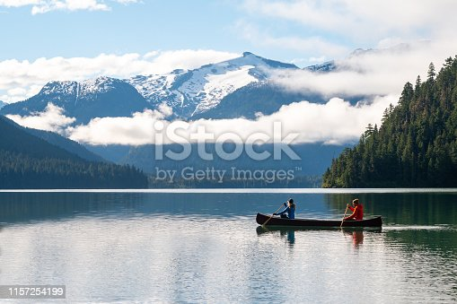 Couple canoeing on lake against beautiful mountain. Man and woman enjoying vacation in Whistler. View of stunning nature.